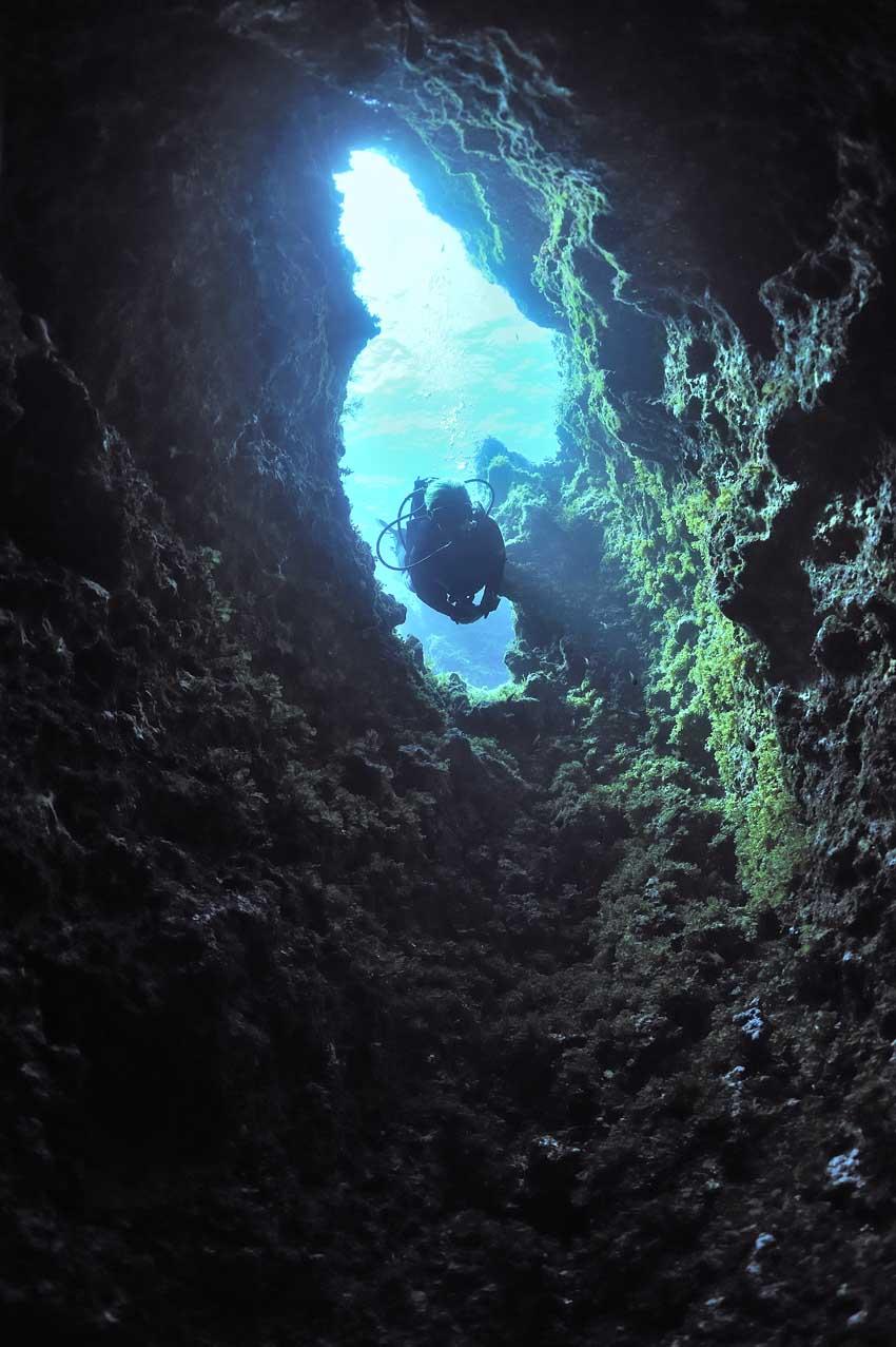 Plongeur à l'entrée d'une faille dans la roche - Diver in the en