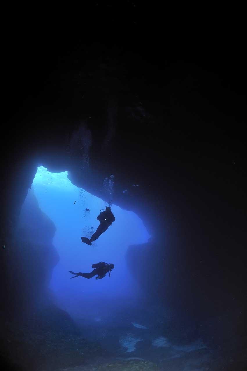 Plongeurs à l'entrée d'une grotte sous-marine - Divers at the en