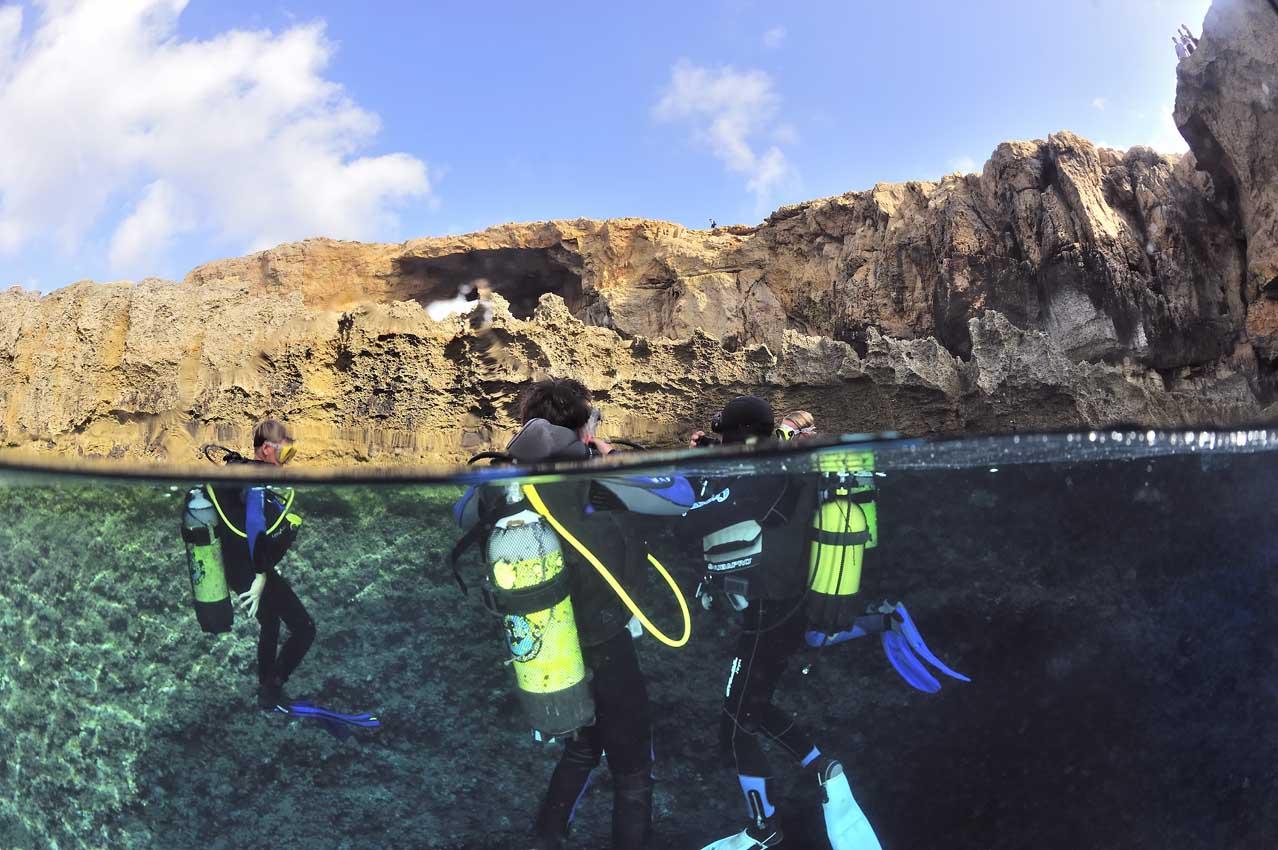 Plongeurs devant une arche rocheuse - Divers in front of a rocky