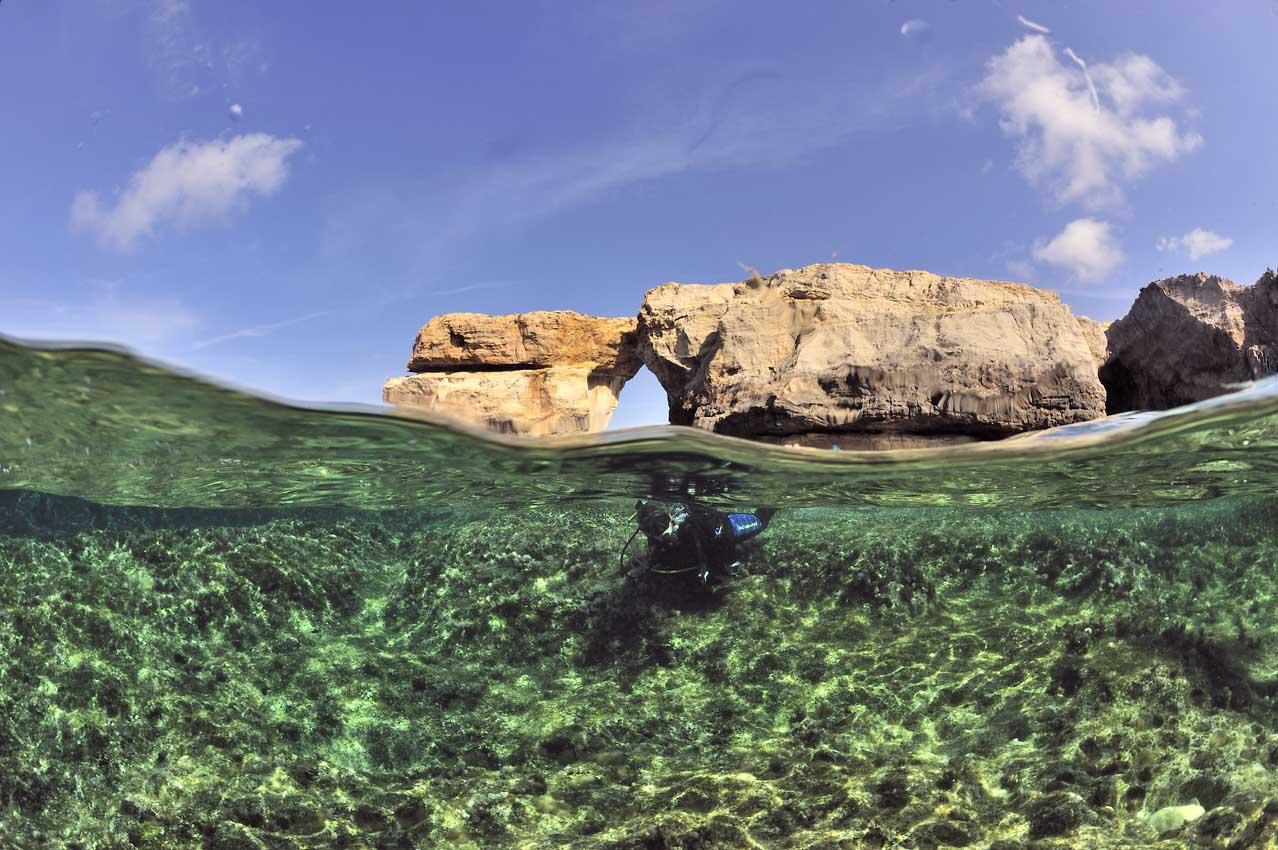Un plongeur devant une arche rocheuse - A diver in front of a ro